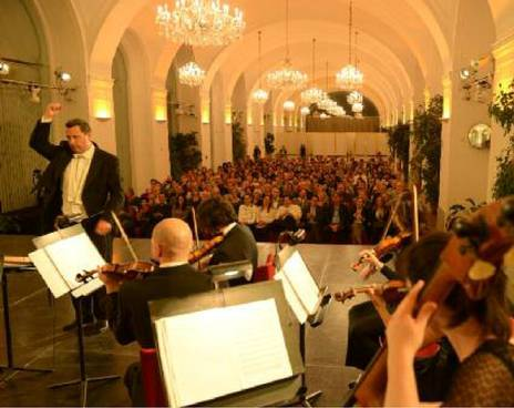 The Schoenbrunn Palace Orchestra during a concert. View of the conductor, other musicians, and the audience from the orchestra in the Schoenbrunn Orangery Vienna