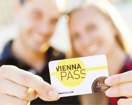 2人のコンサートの観客がウィーンパスを手に持っています。ウィーンパスで60ヶ所以上もの観光名所に入場することができます。