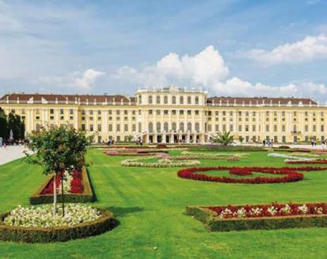 Das Schloss Schönbrunn Wien. Blick aus dem Garten auf das Schloss. Davor sieht man den schön gepflegten Garten mit Blumen.