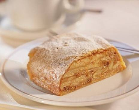 A slice of apple strudel on a plate with coffee. The image represents the package dinner and concert