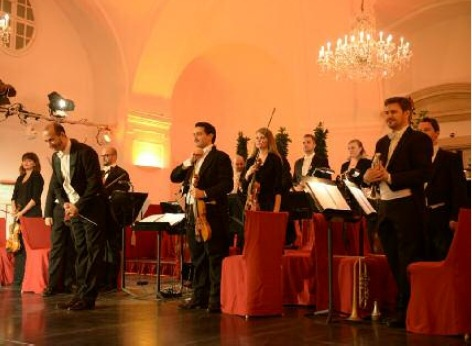 The musicians of the Schoenbrunn Palace Orchestra after the concert. The conductor bows, the musicians are enjoying the applause