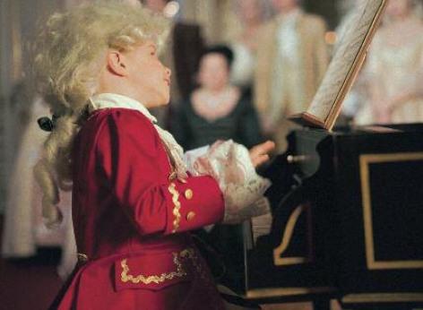 La imagen muestra a un joven ante una espineta, simboliza al joven Wolfang Amadeus Mozart, cuya música suena en los conciertos clásicos diarios de la orquesta del Palacio de Schönbrunn en la Orangerie de Viena