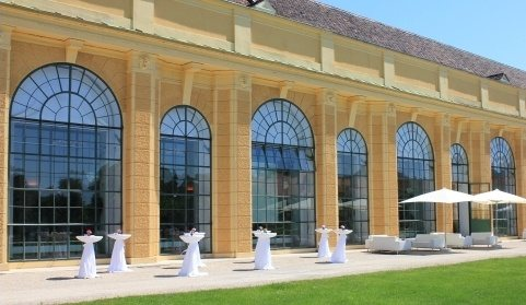 The Orangery Vienna with arched windows in the background and tables and lounges set up in the garden in the forecourt, ideal for an aperitif before a concert of the Schoenbrunn Palace Orchestra