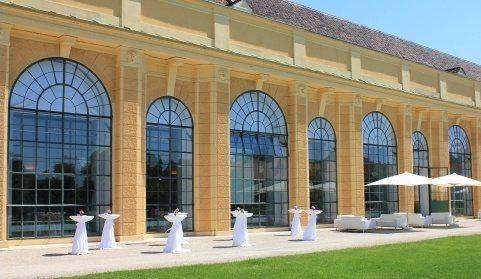 背景にアーチ型の窓のウィーン・オランジェリーがあり、庭園中庭にバーテーブルや休憩所が設置されています。シェーンブルン宮殿劇場管弦楽団のコンサートの前のアペリティフにぴった