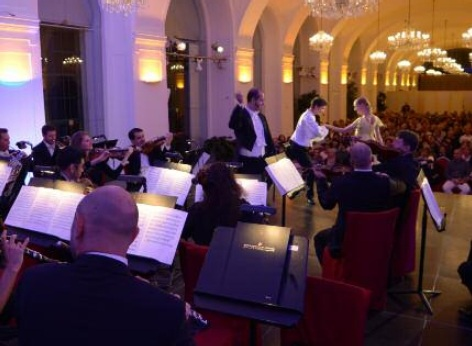 Musicians of the Schoenbrunn Palace Orchestra while performing classical music by Mozart and Strauss. Accompanied by a dancing couple. The photo was taken in the Schoenbrunn Orangery in Vienna