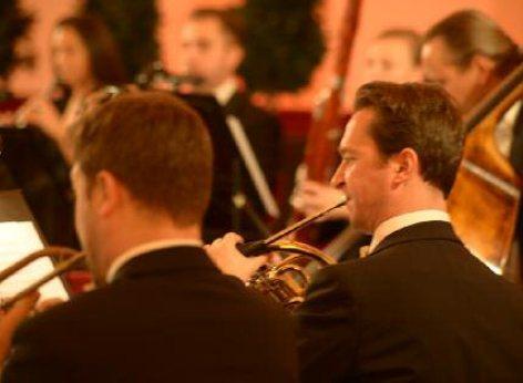 Man sieht 2 Bläser des Schloss Schönbrunn Orchesters während des Konzerts. Im Hintergrund verschwommen einige andere Musiker.