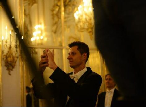 A visitor of the Schoenbrunn Palace concert taking a photo with his mobile to keep lasting memories of this wonderful evening
