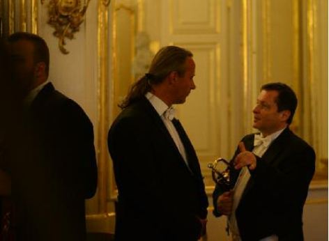 2 musicians of the Schoenbrunn Palace Orchestra before the performance. They are discussing the last details of the classical concert.