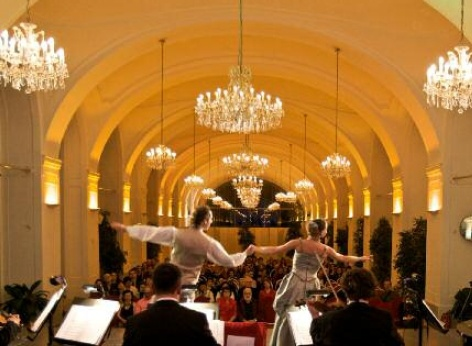 Schoenbrunn Orangery Palace - event venue for classical concerts in the Orangery. In the foreground, the musicians of the Schoenbrunn Palace Orchestra, in the centre the dancing couple, with the audience behind
