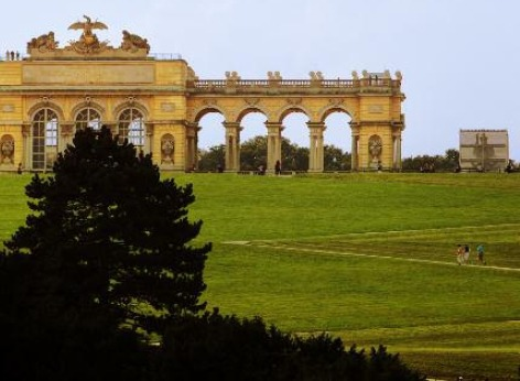 The famous gloriette of Schoenbrunn Palace. The left part of the building is visible, as is the centre. Before that, tourists are climbing the small hill