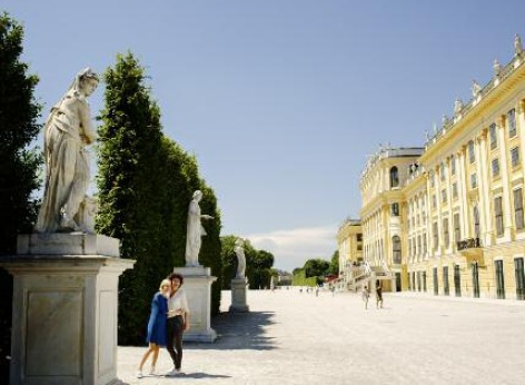 The tourist attraction Schoenbrunn Palace in Vienna. The palace is to the right, two tourists taking a photo of the garden on the left