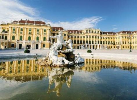 Come sfondo si vede il castello di Schönbrunn a Vienna, in primo piano la fontana piena d'acqua