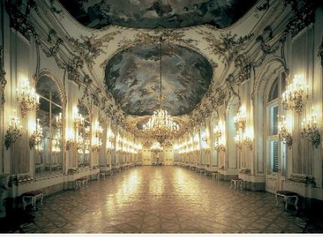 A ceremonial hall in Schoenbrunn Palace, many candle chandeliers on the walls to the left and right are brightly lit, the magnificent paintings on the ceiling are visible